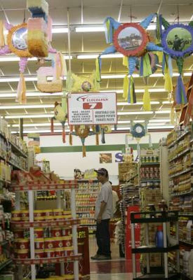 Joaquin Cruz takes in the assortment of imported products from Mexico and Central America at Supermercados Teloloapan in southwest Houston. Photo: Julio Cortez, Houston Chronicle
