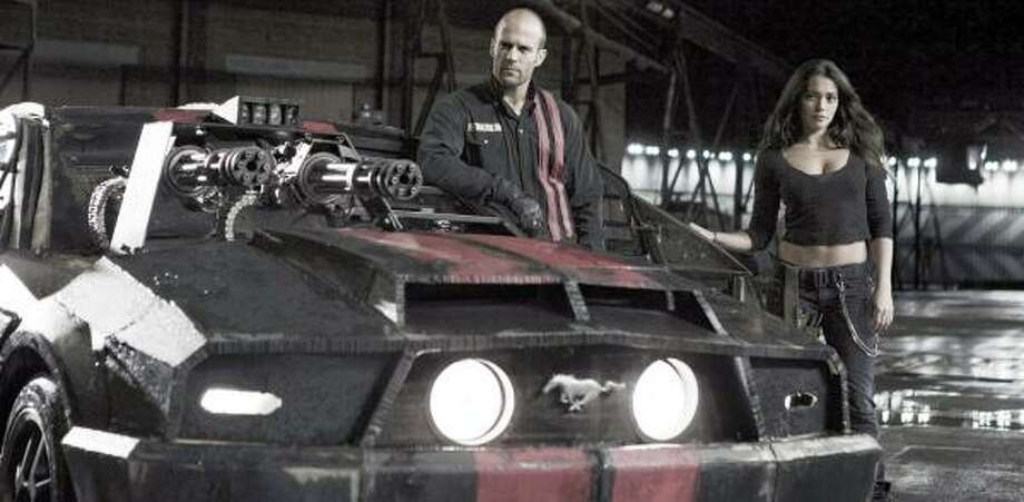 In Death Race, Jensen Ames (Jason Statham) and his navigator, Case (Natalie Martinez), prepare for a race in his modified Mustang V8 Fastback. Photo: TAKASHI SEIDA, Takashi Seida