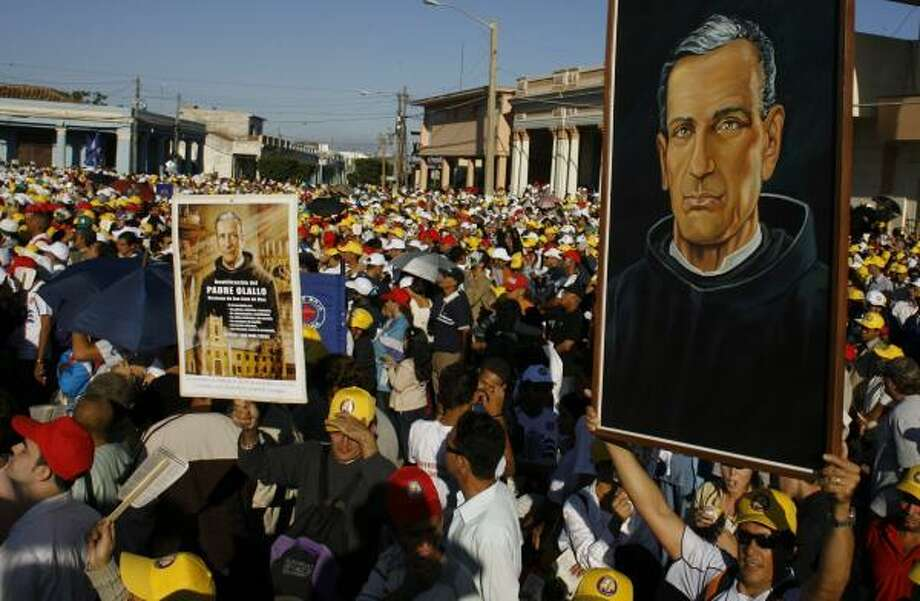 Catholics hold up images of Friar Jose Olallo Valdes during his Mass of Beatification on Saturday in Camaguey, Cuba. The ceremony is the first beatification in Cuba, and is the last step before canonization, when the church recognizes a person as a saint. Photo: JAVIER GALEANO, ASSOCIATED PRESS