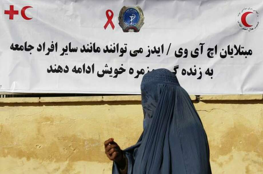 "An Afghan woman walks past a banner about aid on World AIDS Day in Kabul on Monday. The banner says that people affected by HIV/AIDS ""can continue their lives in society."" Photo: RAHMAT GUL, ASSOCIATED PRESS"