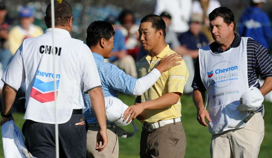 Anthony Kim, second right, shakes hands with pairing partner K.J. Choi after finishing the 18th hole Saturday. Photo: ROBYN BECK, AFP/Getty Images
