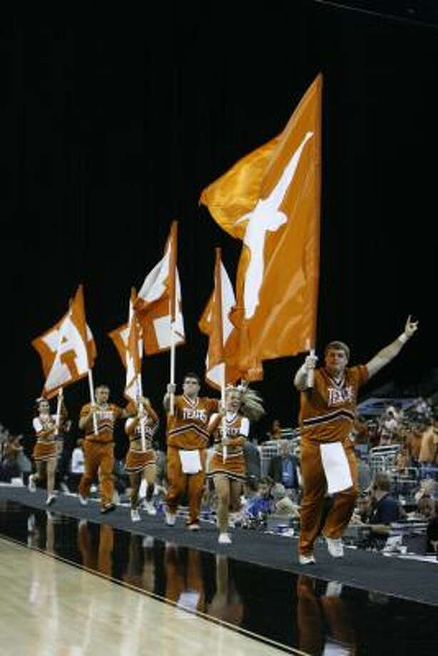 UT cheerleaders run along the court at Reliant Stadium on Friday during the Texas-Stanford game. Photo: Nick De La Torre, Chronicle