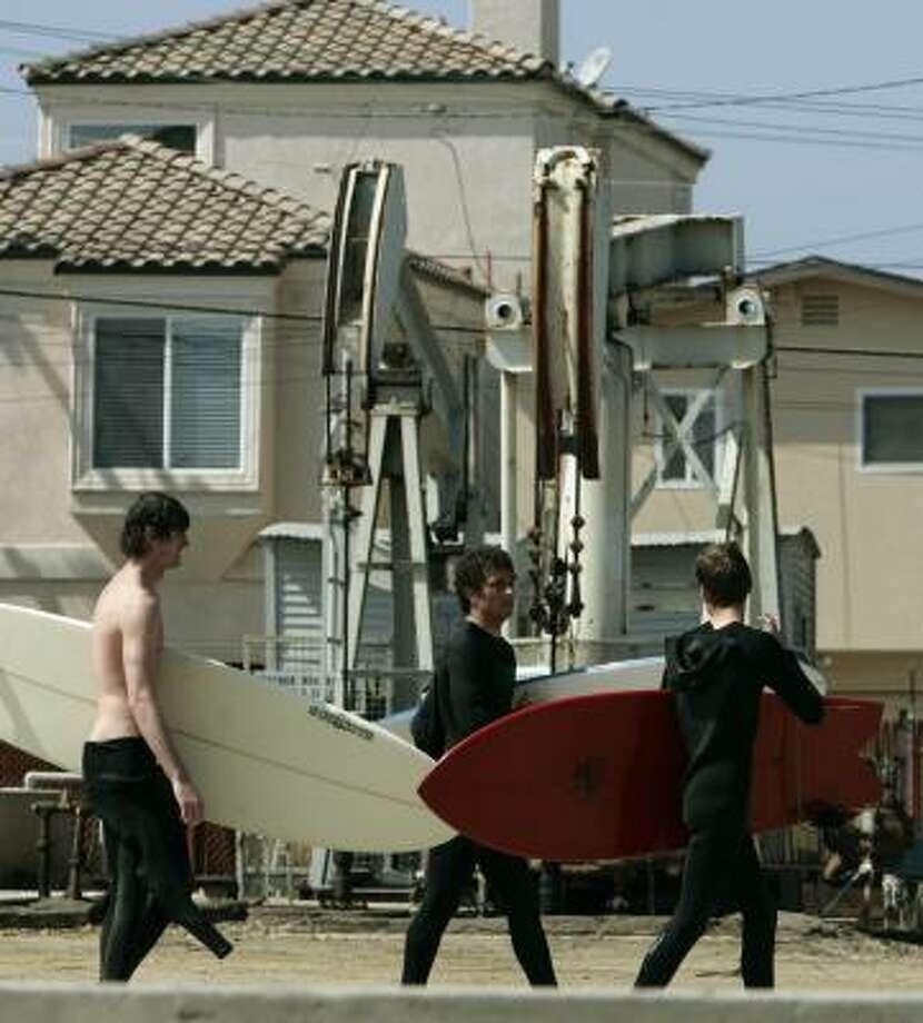 Surfers pass pump jacks near homes in Huntington Beach, Calif. Photo: REED SAXON, ASSOCIATED PRESS