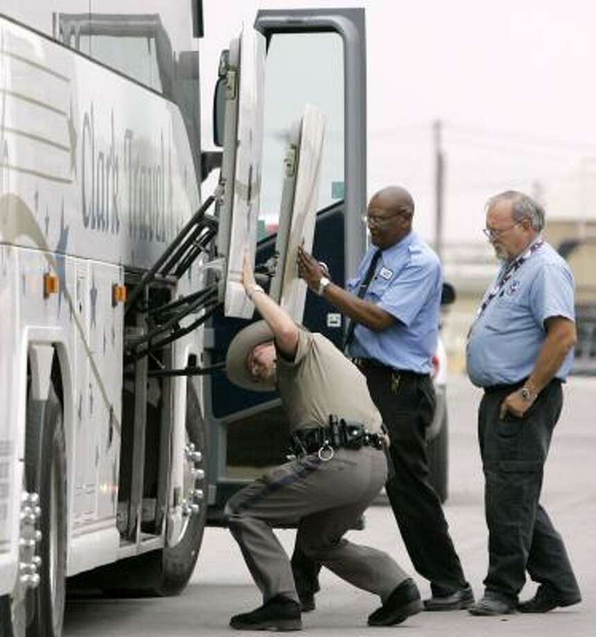 A state trooper checks the cargo hold of a bus Wednesday at the San Angelo Coliseum, where some children and parents from the Yearning for Zion Ranch are being temporarily housed. Photo: TONY GUITIERREZ, ASSOCIATED PRESS