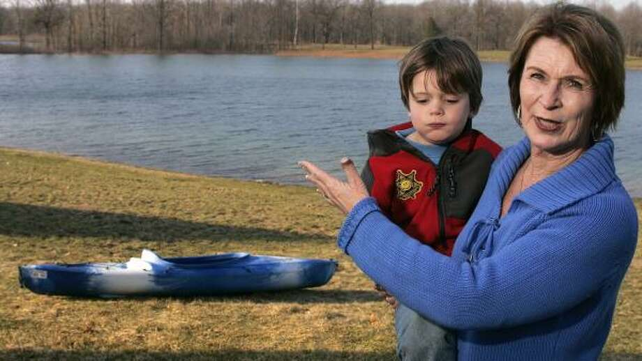 Joan VanZee dragged her kayak out into Versluis Lake behind her home in Plainfield Township, Mich., after her 4-year-old grandson Carter Louisell told her there was a man in the water. Photo: REX LARSEN, AGENCY
