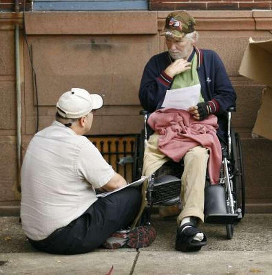 VA outreach nurse Mark Salvatore, left, talks with homeless Vietnam veteran William Joyce in Philadelphia last fall. Photo: MATT ROURKE, ASSOCIATED PRESS FILE