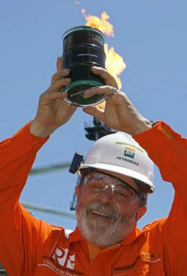 Brazilian President Luiz Inacio Lula da Silva shows off the first oil retrieved from a layer of subsalt. Photo: ERALDO PERES, ASSOCIATED PRESS