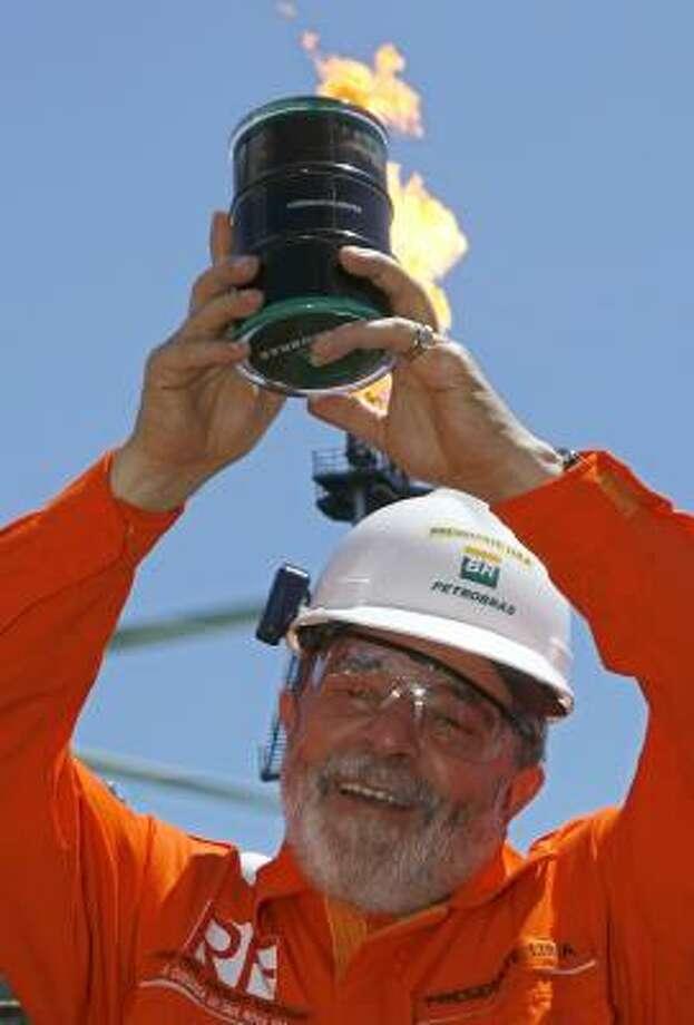 Brazilian President Luiz Inacio Lula da Silva shows off the first oil retrieved from a layer of subsalt. Photo: ERALDO PERES, ASSOCIATED PRESS