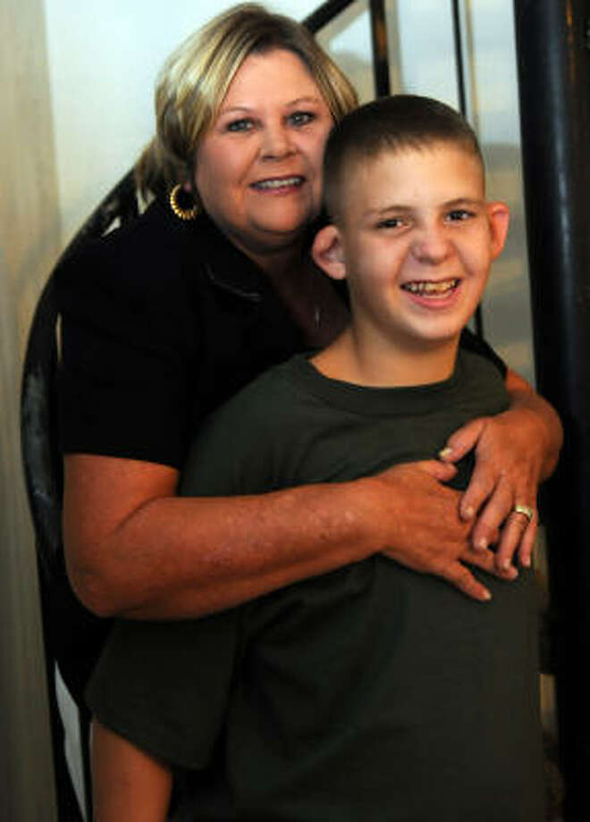 "IN LOVING ARMS: Donna Askew is the grandmother of C.J. ""Simba"" who is a 15-year old child with autism. She is raising the child in her Crosby home and takes him to school in the Heights. Photo: Kim Christensen, FOR THE CHRONICLE"