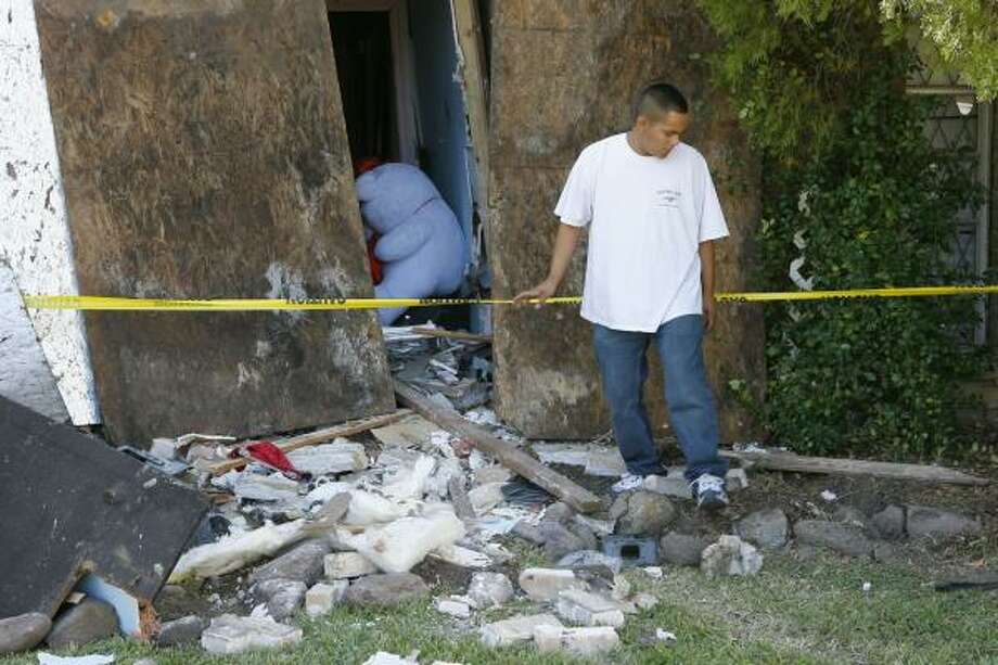 Edwin Martinez inspects the damage after an SUV slammed into a southwest Houston home. Photo: STEVE CAMPBELL PHOTOS, CHRONICLE