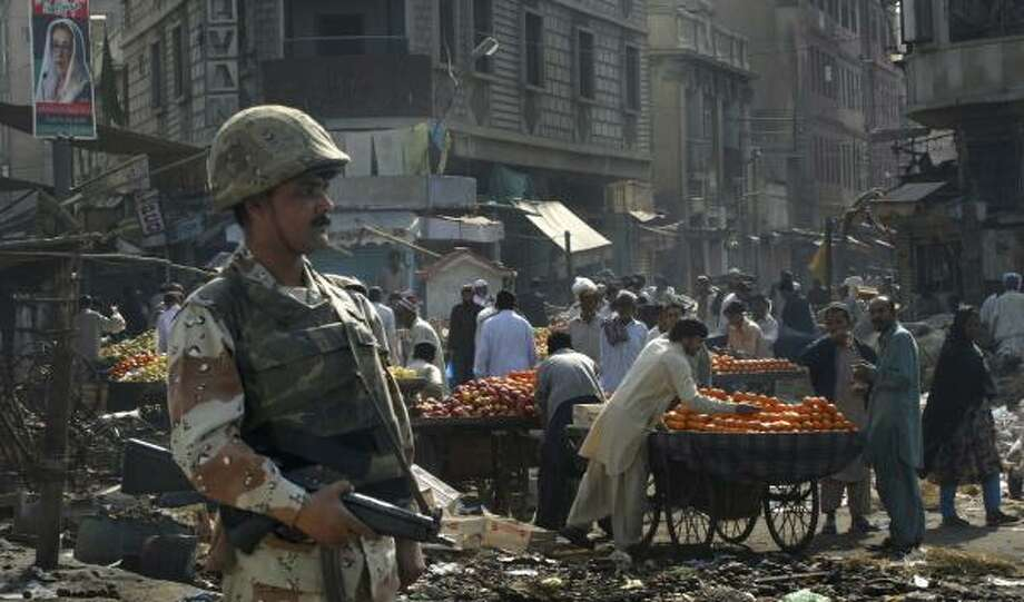 A Pakistani soldier stands guard in a Karachi market on Monday to allow shopkeepers to reopen following recent violence. Photo: DAVID GUTTENFELDER, ASSOCIATED PRESS