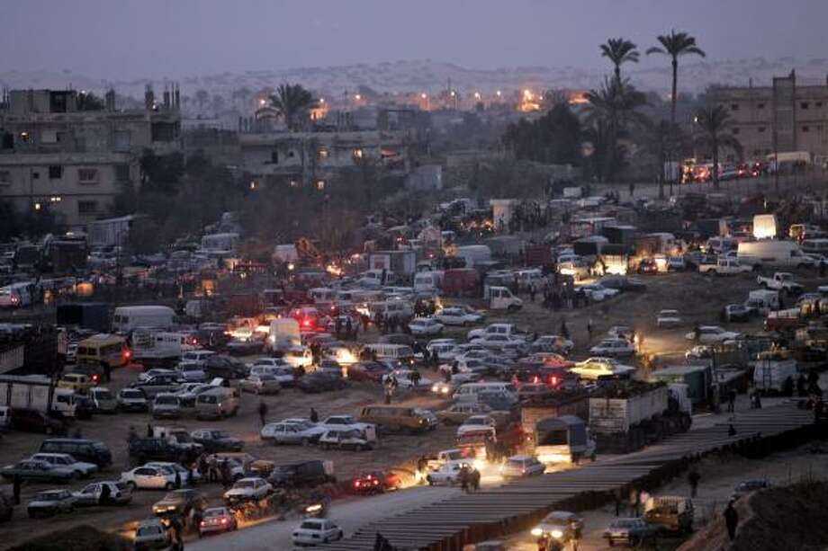 Palestinian vehicles trying to cross into Egypt form a massive jam Saturday in Rafah, on the border between the Gaza Strip and Egypt. Egyptian riot police and armored vehicles restricted Gaza motorists to a small border area, in the second try in two days to restore control. Photo: LEFTERIS PITARAKIS, ASSOCIATED PRESS