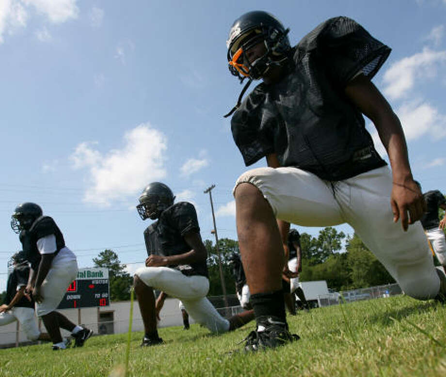 North Forest High School running back Dereck Alex, right, and his teammates perform forward lunge drills between a team scrimmage. Photo: Thomas B. Shea, For The Chronicle