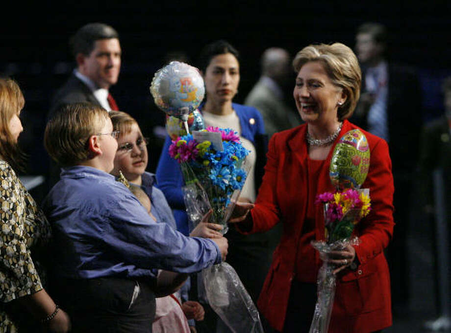 Hillary Clinton accepts flowers and balloons from some children who attended her speech at the Greater Houston Partnership energy summit at the George R. Brown Convention Center on Thursday. Photo: Steve Campbell, Chronicle