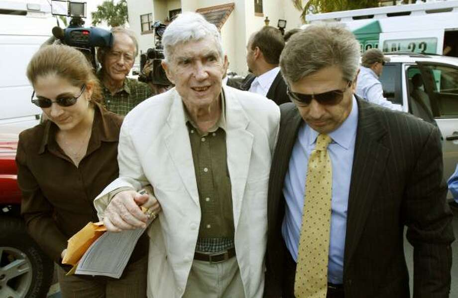 Luis Posada Carriles is assisted by his daughter, Janet Arguello, and attorney, Arturo Hernandez, in Miami. Posada is accused of terrorism, but his attorney says the octogenarian is an innocent man in poor health who wants to spend the rest of his life in Miami among family, friends and exiles. Photo: WILFREDO LEE, ASSOCIATED PRESS FILE