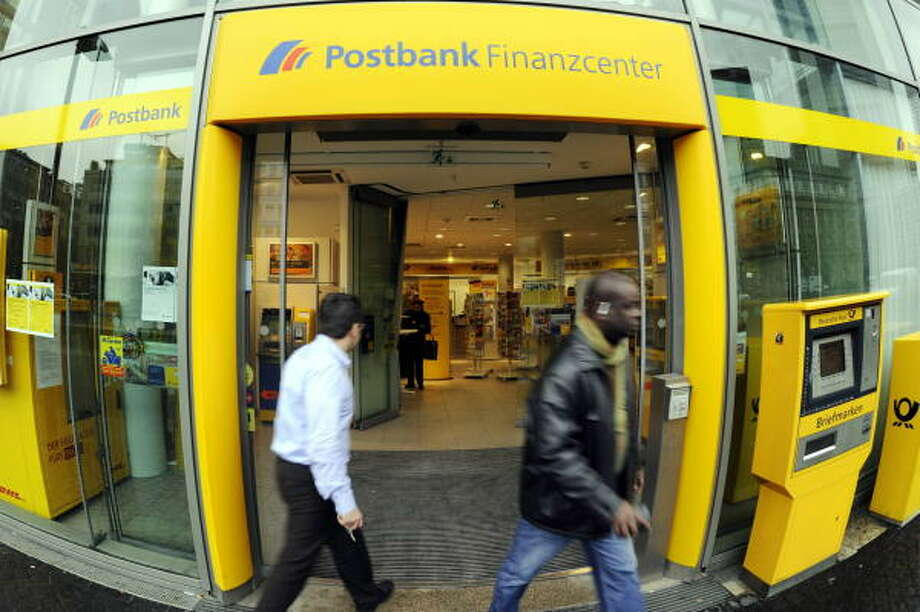 Clients leave a subsidiary of German bank Postbank earlier this week in Frankfurt. The euro, once a powerhouse currency against the dollar, fell to its lowest level this week since April 2006. Photo: THOMAS  LOHNES, AFP/GETTY IMAGES
