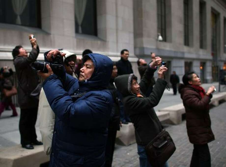 Tourists shoot pictures in front of the New York Stock Exchange on Thursday. Inside, stocks rose, with the Dow Jones industrial average up more than 100 points. Photo: SPENCER PLATT, GETTY IMAGES