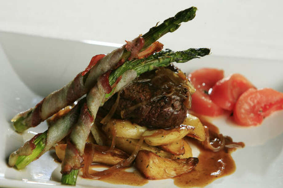 Chef Young Cheal Kim's filet mignon with a Korean soy reduction comes with fingerling potatoes and bacon-wrapped asparagus. Photo: Eric Kayne, Chronicle