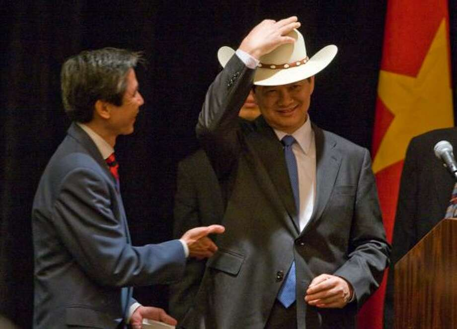 Joe Knierien, left, of the International Trade Expo, gives Vietnamese Prime Minister Nguyen Tan Dung a Stetson cowboy hat during the Discover Vietnam U.S. & Vietnam Business Forum luncheon on Thursday. Photo: Nick De La Torre, Chronicle