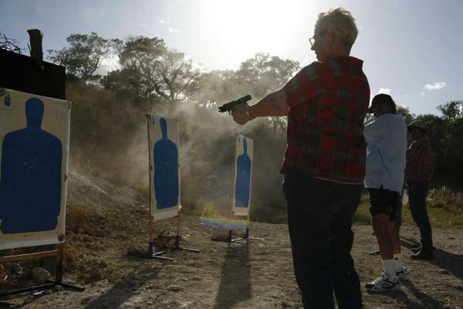 Firearms instructor Mike Cox offers a discount to college students who take his course in order to obtain a license to carry a concealed weapon. In addition to the target practice sessions, like this one recently on a ranch near Blanco, a classroom session is required. Photo: LISA KRANTZ, SAN ANTONIO EXPRESS-NEWS