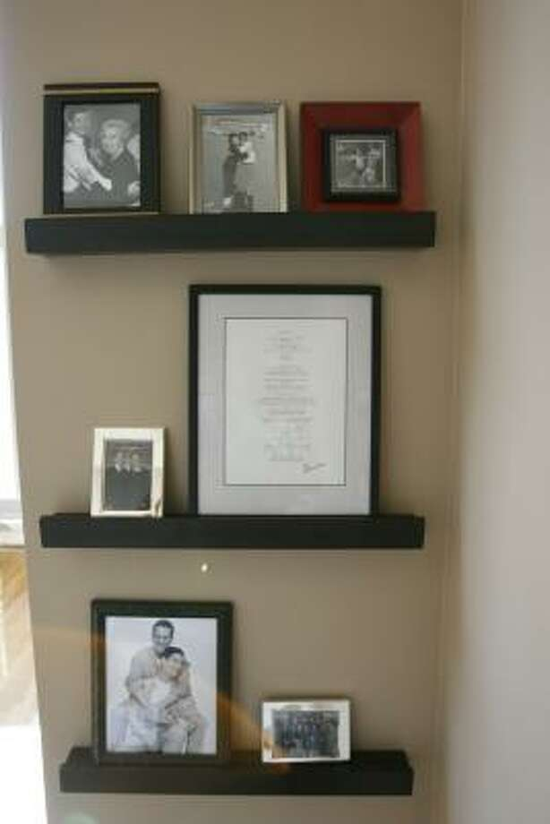 Wall shelving gives you the freedom to rotate in new photos and memorabilia. Photo: Buster Dean, Houston Chronicle