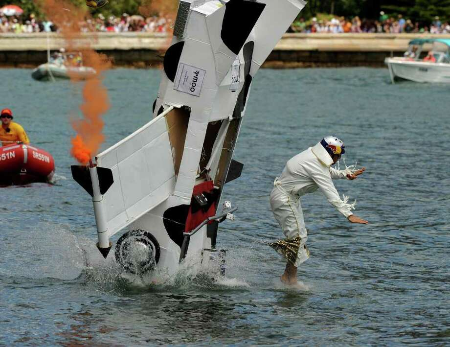 "Pilot Hank Opdam jumps from the Cadillac of his ""4 Fat Elvises"" team as it hits the water during the Red Bull Flugtag event in Sydney on November 7, 2010. Photo: GREG WOOD, AFP/Getty Images / 2010 AFP"
