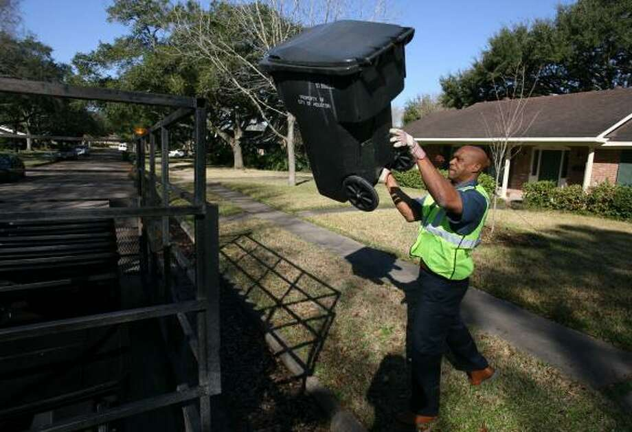 """EL Pleasant tosses a damaged trash can into his trailer last week in Houston. The city worker delivers replacement cans to Houston residents. Trash can theft is an ongoing problem in the city, police say. But Pleasant sees a bright side to the thievery: """"Job security."""" Photo: SHARÓN STEINMANN, CHRONICLE"""