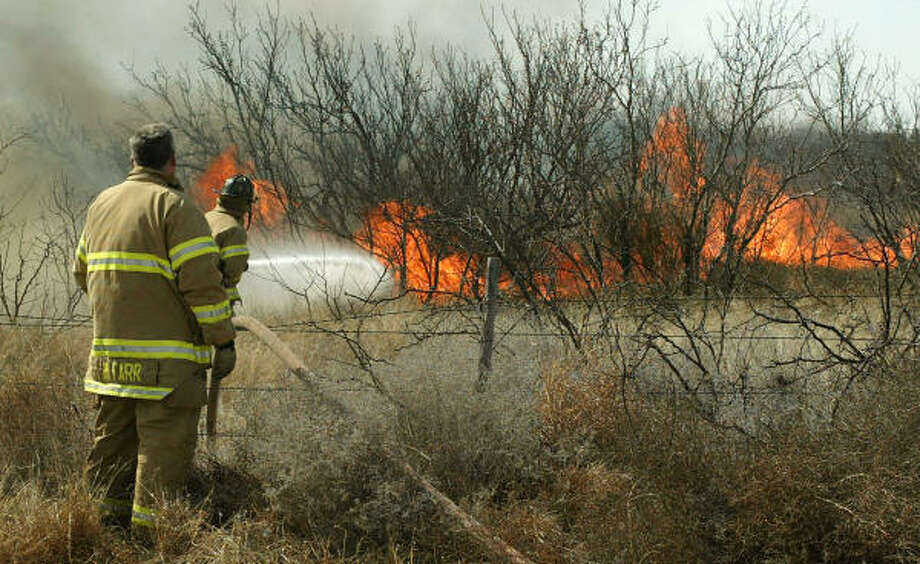 Firefighters confront flames from a range fire south of Odessa that has burned more than 7,000 acres and threatened homes that were briefly evacuated on Monday. Photo: Mark Sterkel, Odessa American