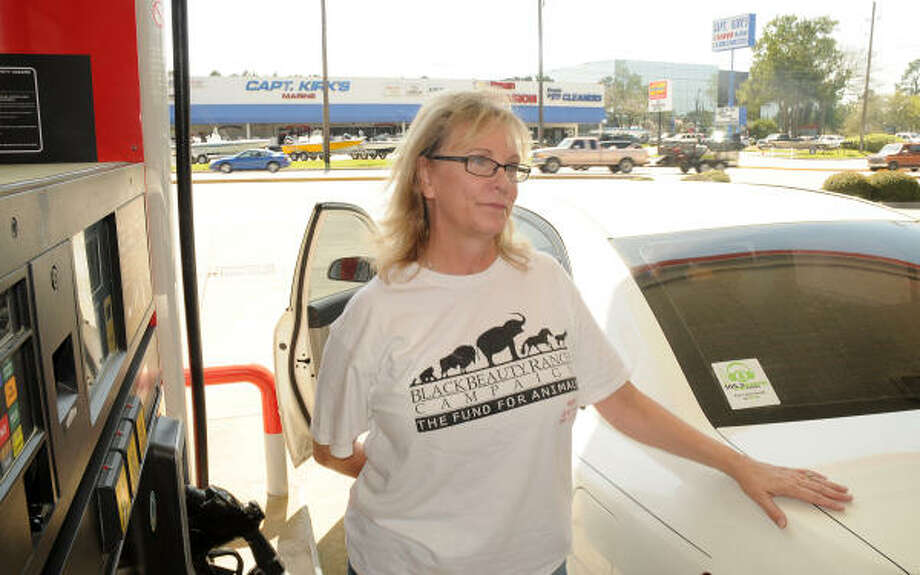Cheryl Meyer, Magnolia, fills her economy car with gas at a Texaco Station on Sawdust Road. She has changed her driving habits because of the high gas prices. Photo: David Hopper, For The Chronicle