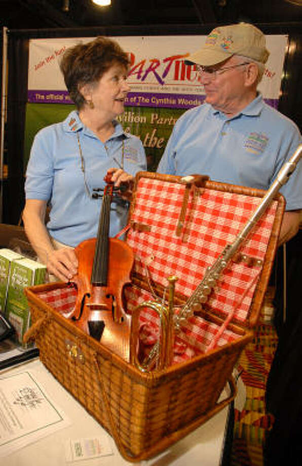 Cynthia Woods Mitchell Pavilion Partners members Letty and Tom Kelly fix the musical picnic basket during the South Montgomery County Woodlands Chamber of Commerce's Business Expo. Photo: David Hopper, For The Chronicle