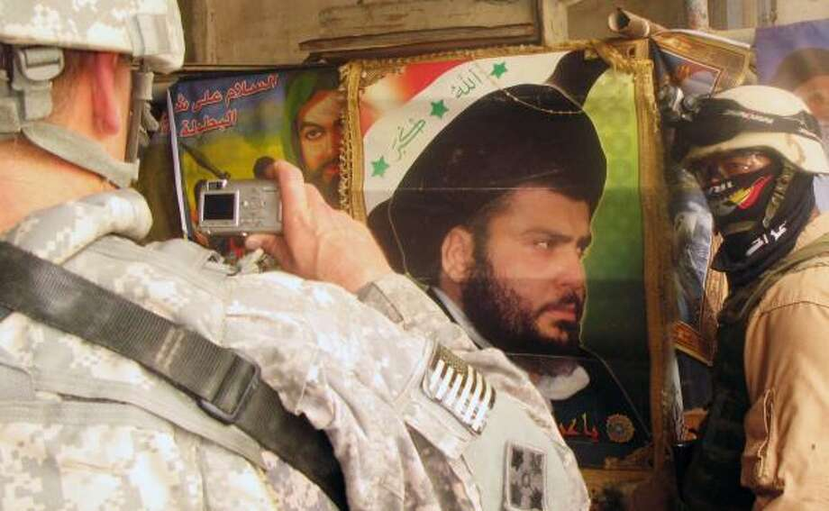 U.S. troops examine a poster of cleric Muqtada al-Sadr and items discovered during a raid Monday in Basra. Photo: KIM GAMEL, ASSOCIATED PRESS