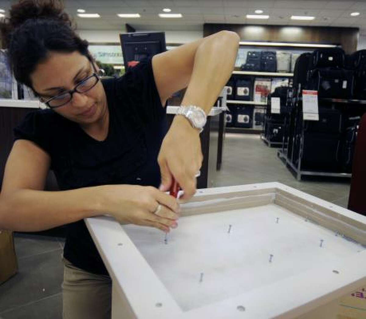 Jackie Silva, a visual assistant, prepares a floor display for the new Macy's store in Pearland Town Center. The store opens on Wednesday.