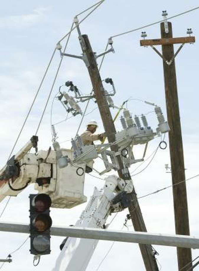 Centerpoint Energy's Shane Sobnosky works on replacing a power line as he and his crew work to restore power in the aftermath of Hurricane Ike on , Sept. 16 in Galveston. Photo: Brett Coomer, Chronicle