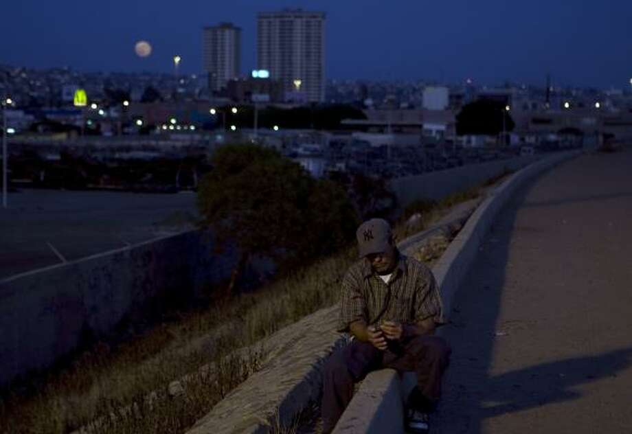 A deportee sits near the dry Tijuana River basin on the Mexican side of the border in Tijuana, Mexico. Here, the deported, the would-be border crossers, the smugglers and the drug addicts gather to swap stories and hope for a lucky break up north. Photo: GUILLERMO ARIAS, ASSOCIATED PRESS