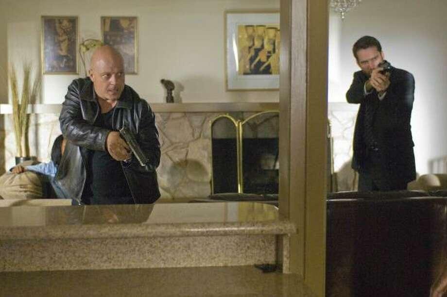 Det. Vic Mackey (Michael Chiklis, left) and Det. Ronnie Gardocki (David Rees Snell) take aim in the series finale of the FX drama The Shield. Photo: Prashant Gupta, AP