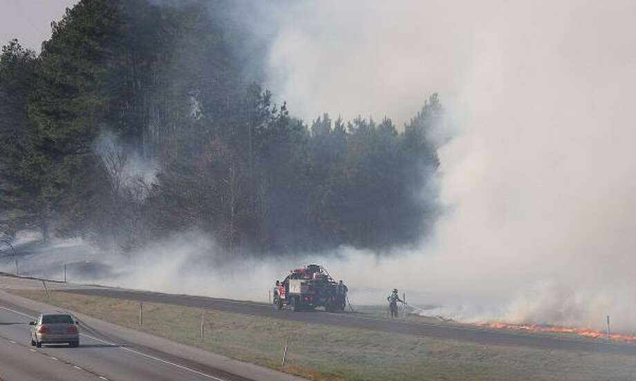 Sabine volunteer firefighters tackle a brush fire along I-20 east of Tyler last month. Photo: HERB NYGREN JR., TYLER MORNING TELEGRAPH