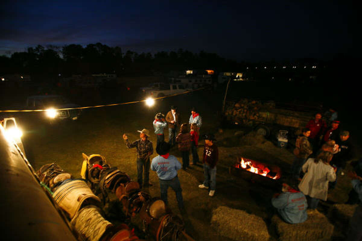 Participants in the Sam Houston Trail Ride enjoy themselves after setting up camp near Magnolia on Monday night.
