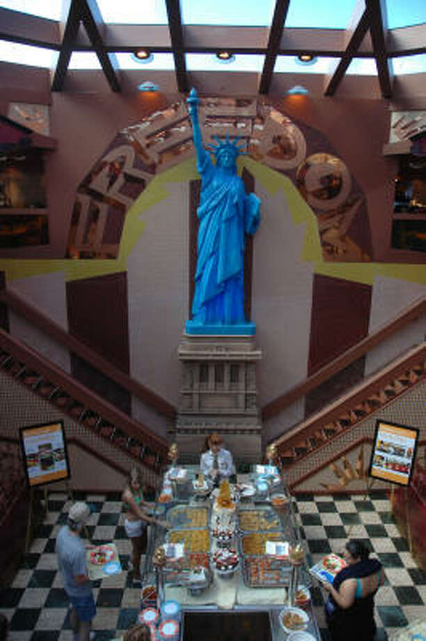 Architect Joe Farcus, known for his imaginative cruise-ship designs, has given an eclectic look to the Carnival Freedom's casual eatery with a huge Statue of Liberty sculpture presiding over two levels of food stations. Photo: Joan Shattuck