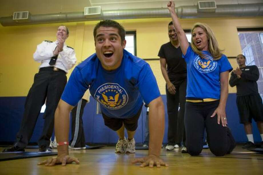 Bernie Salazar, a former contestant on The Biggest Loser, does push-ups as acting Surgeon General Dr. Steven Galson, left, and fitness expert Denise Austin, right, cheer during the launch of the President's Council on Physical Fitness and Sports new national adult fitness test. Photo: BRENDAN HOFFMAN, ASSOCIATED PRESS