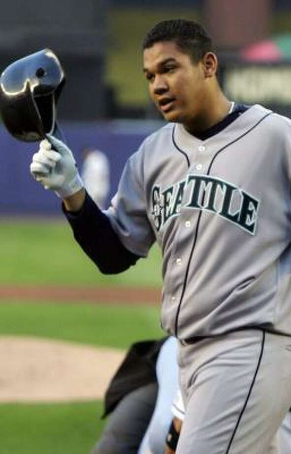 Mariners pitcher Felix Hernandez heads to the dugout, left, after hitting a grand slam in the second inning, but the game didn't have a happy ending for Hernandez as he leaves in the fifth after suffering a sprained ankle. Photo: Jim McIsaac, Getty Images