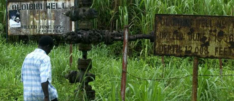 Robert Nadioni, a surveyor, approaches Oil Well No. 1 near Oloibiri, Nigeria. The villages of Oloibiri and Otabagi are sparring over a rusty well that has not produced in three decades. Photo: SUNDAY ALAMBA, ASSOCIATED PRESS
