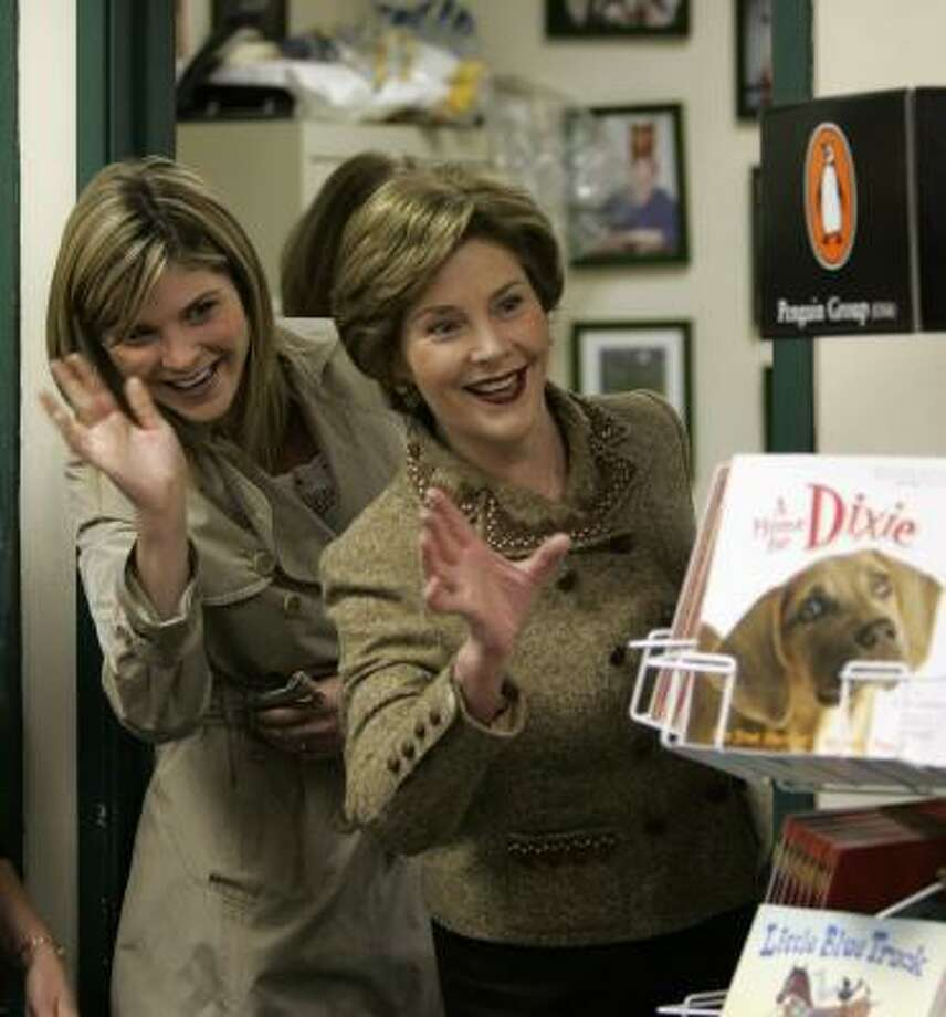 First lady Laura Bush and her daughter Jenna wave to people waiting in line at a bookstore in Glen Rock, N.J., for a book signing for the children's book they co-authored, Read All About It! Photo: MIKE DERER, Associated Press
