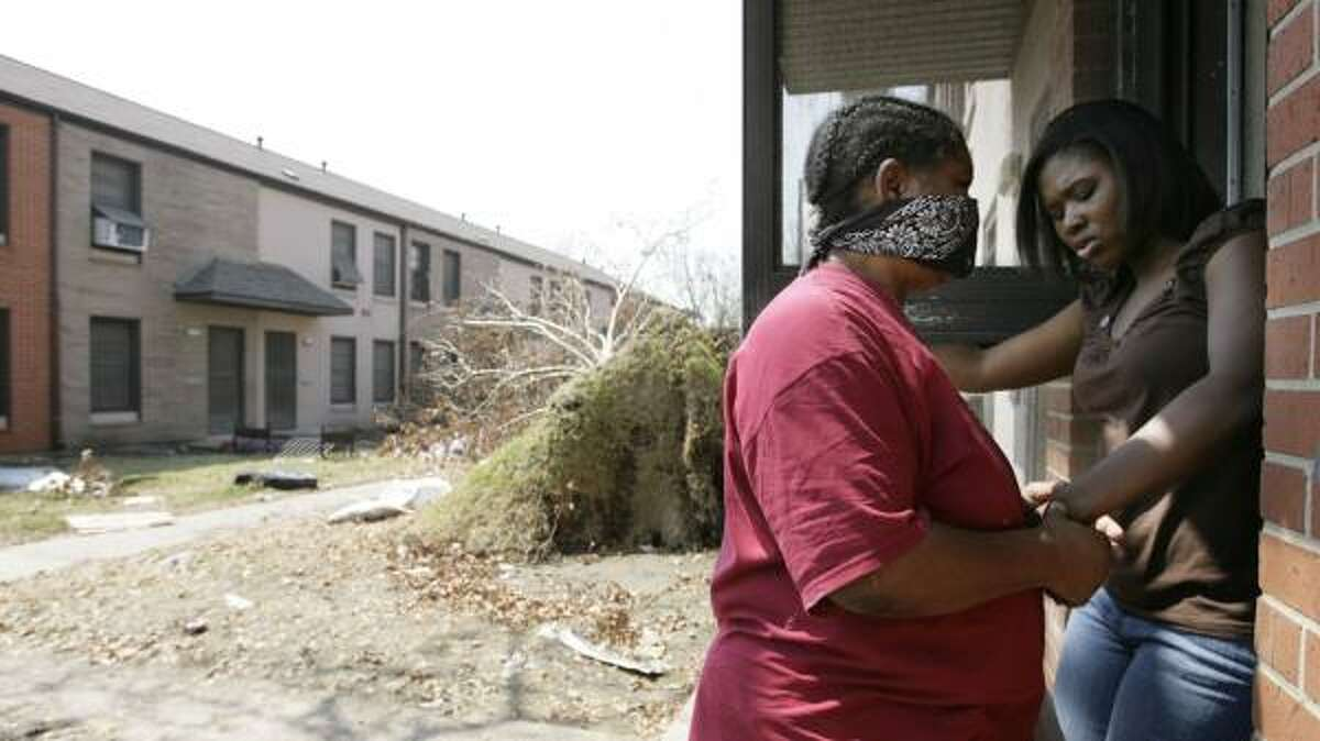 Stephany Brown, right, helps her blind aunt, Sarah Horn, last month at Horn's condemned apartment in the Oleander Homes public housing complex in Galveston. Many residents who were forced out by hurricane damage are uncertain of their next move.