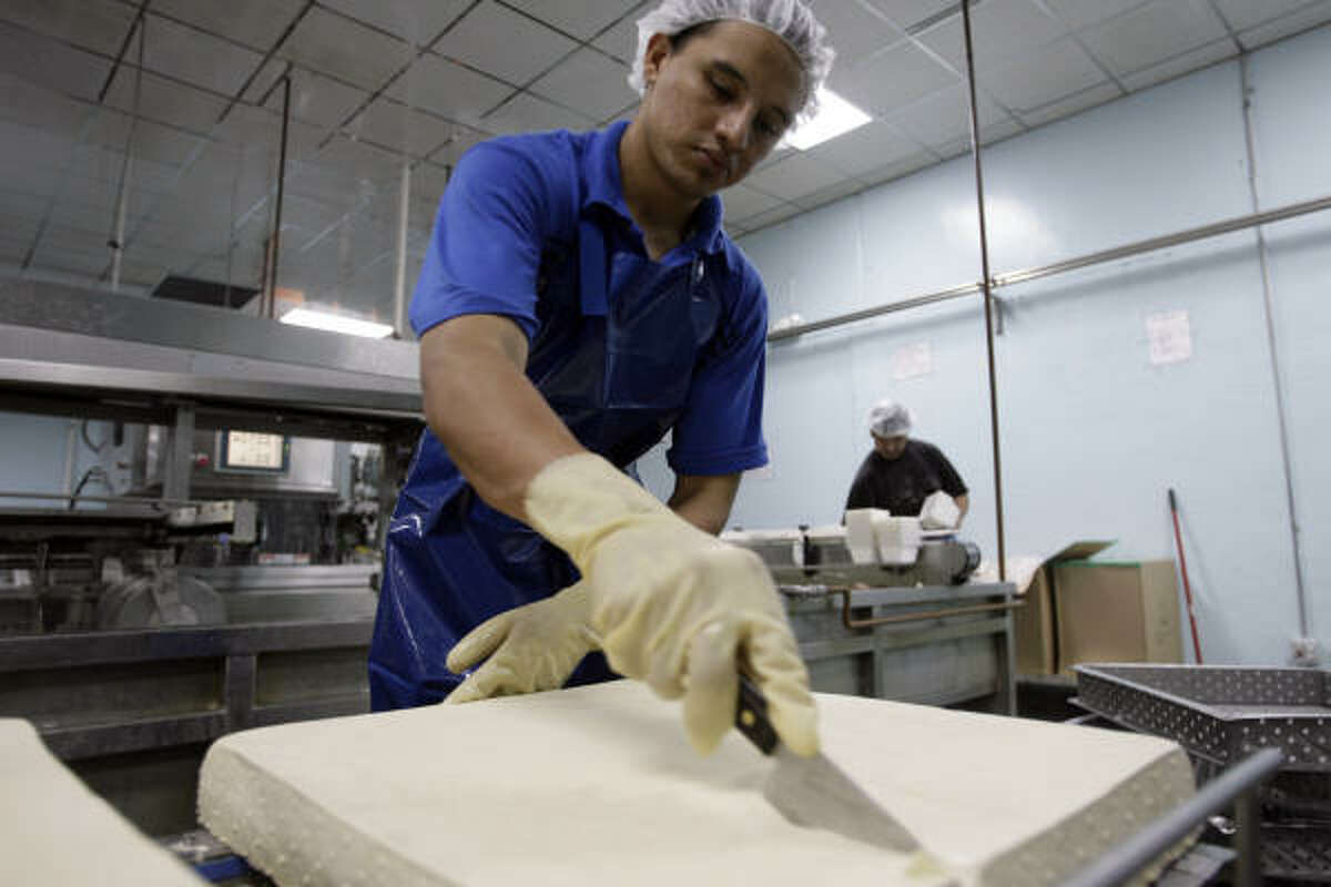 Ramon Torres cuts tofu at Banyan Foods. In 2005, the Chiu family began making tamales of tofu instead of more traditional fillings like chicken, pork and beef.