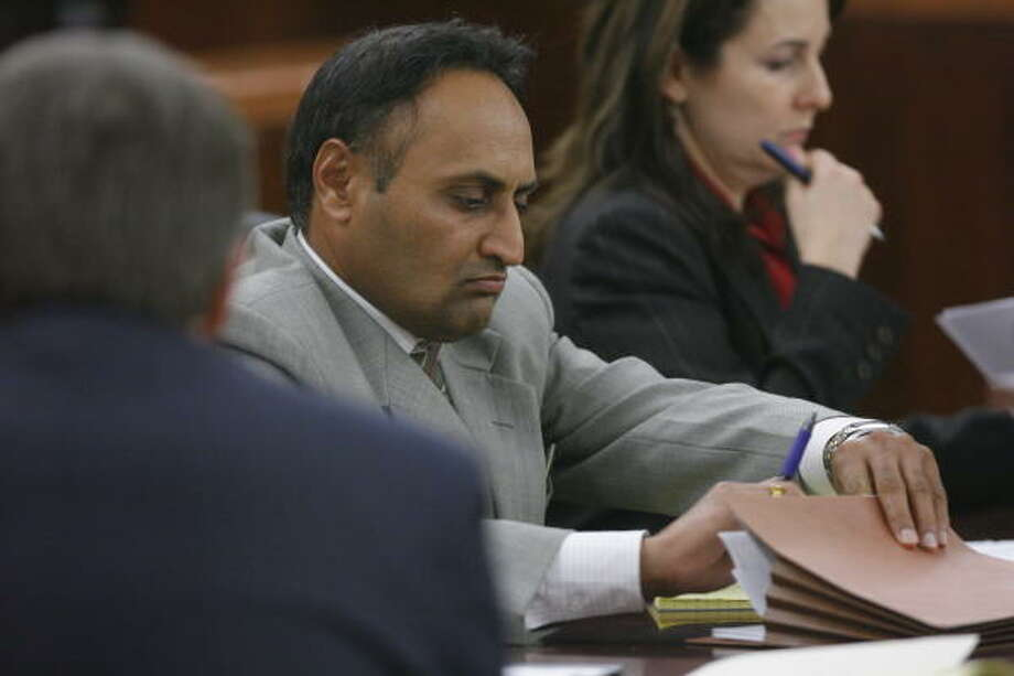 Hardeep Grewal reaches for paperwork as he listens to testimony during his trial Tuesday in Houston in the death of his daughter's boyfriend,  Nitin Sarangapani. Photo: Steve Campbell, Chronicle