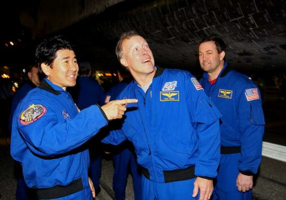 Mission specialist Takao Doi of Japan, left, talks with mission commander Dom Gorie and mission specialist Michael Forman after Endeavour landed Wednesday night. Photo: Stan Honda, AP