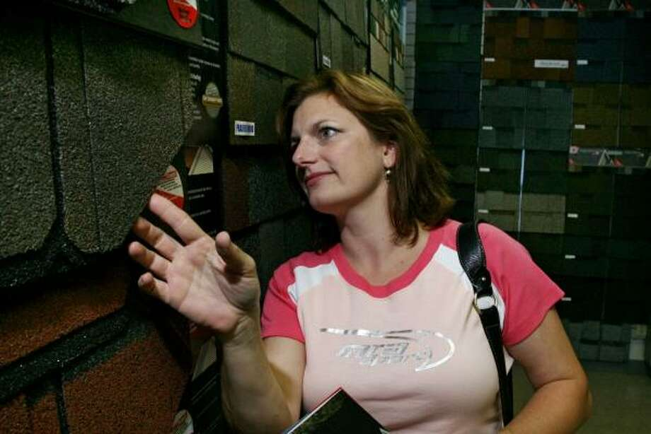 Deb Freitag looks at roofing materials at a Cincinnati roofing store. Photo: Tom Uhlman, AP