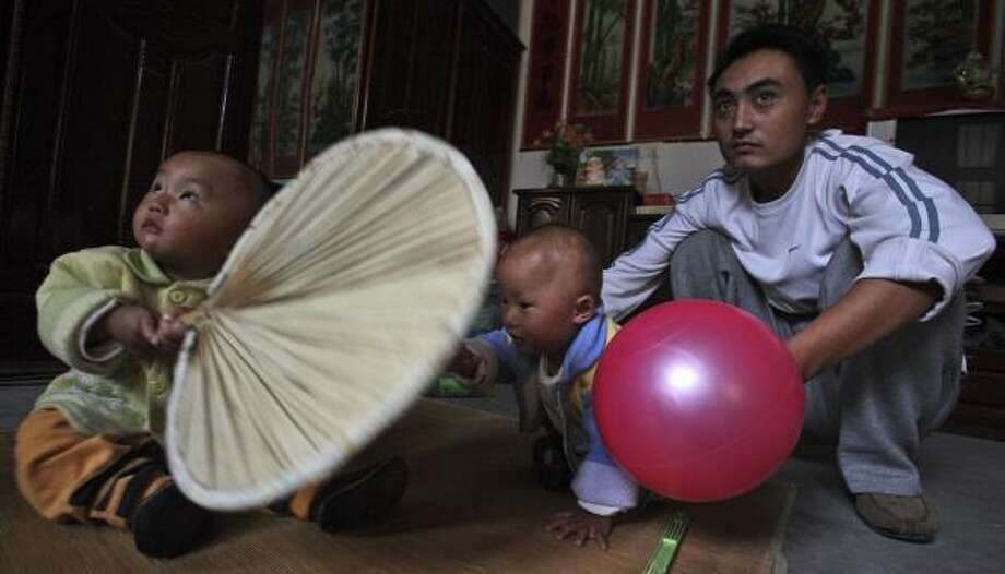 Zhang Peng, left, and twin Zhang Xue play Wednesday near their father, Zhang Rongwei, at home. Both children suffered from kidney stones after drinking tainted milk powder products. Photo: NG HAN GUAN, ASSOCIATED PRESS