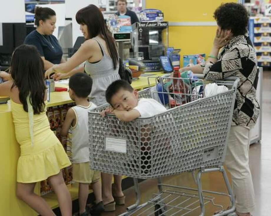 Customers wait for service at one of Wal-Mart Stores' locations in San Jose, Calif. The world's largest retailer said its profit rose 17 percent in the second quarter, and it is increasing its full-year forecast. Photo: PAUL SAKUMA, ASSOCIATED PRESS