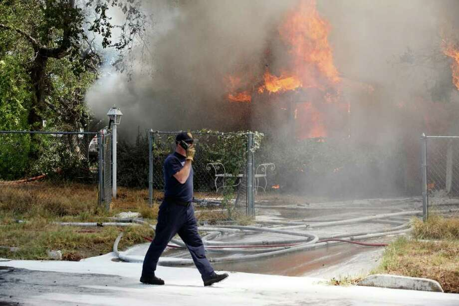 San Antonio firefighters work a house fire at the 1600 block of Kendalia, Monday, Aug. 8, 2011. The fire claimed the life of a 46-year-old male. They were able to rescue five cats from the residence. Photo: JERRY LARA, San Antonio Express-News / SAN ANTONIO EXPRESS-NEWS